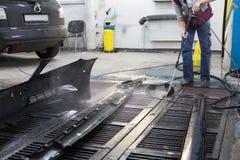 Repairman washes car parts Royalty Free Stock Images