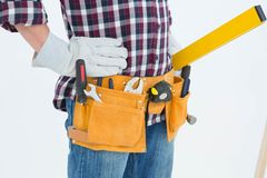 Repairman wearing tool belt while standing with hands on hips. Cropped image of repairman wearing tool belt while standing with hands on hips over white Royalty Free Stock Image