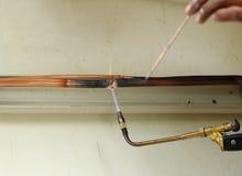Repairman welding copper pipes Stock Photo