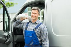 Repairman With White Cable. Happy Repairman With White Cable Coil Standing In Front Of Van Royalty Free Stock Image