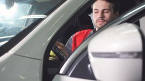 The Repairman, Who Is Dressed in a Working Uniform, Is in the Vehicle and Checks the Gearbox. The Repairman, Who Is Dressed in a Working Uniform, Is in the stock footage