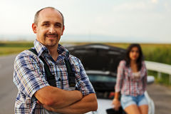 Repairman and woman driver in front of broken car Stock Photo