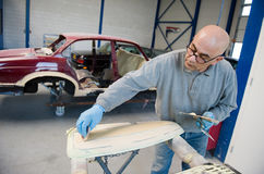 Repairman at work. A car repairman is preparing a part of a carbody for repainting in a garage Stock Photography