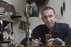 Repairman Working On Clock In Workshop Stock Photo