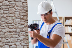 The repairman working with drilling drill perforator Royalty Free Stock Photo