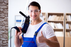 The repairman working with drilling drill perforator Royalty Free Stock Image