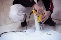 Repairman working with drilling machine. And assambling  furniture Stock Photos