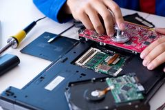 Repairman working in technical support fixing computer laptop tr Stock Images