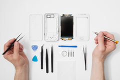 Repairman workplace with phone and tools. Repairman workplace with phone and special tools. Disassembled smartphone with disassembling instruments and repairer Royalty Free Stock Photo