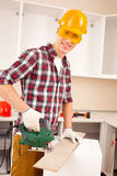 Repairman works jigsaw royalty free stock photo