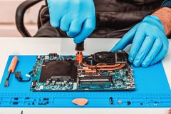 The repairman works in technical support, is engaged in the restoration and cleaning of the laptop royalty free stock photo