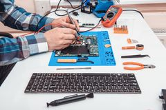 The repairman works in technical support, is engaged in the restoration and cleaning of the laptop royalty free stock images