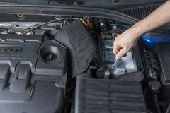 Repairman with wrench checking car battery contacts. Repairman with wrench checking car battery contacts royalty free stock photography