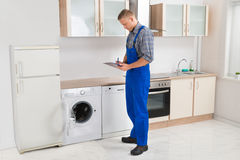 Repairman Writing On Clipboard Stock Images