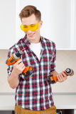 Repairman in yellow safety glasses selects tool Royalty Free Stock Image