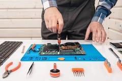 Repairmanen arbetar i teknisk service, kopplas in i ?terst?llandet och lokalv?rden av b?rbara datorn arkivfoton