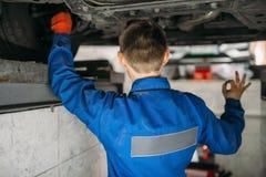 Repairmanen justerar hjulvinklarna av bilen på ställning royaltyfri bild
