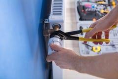 RepairmanFixing Radiator With skiftnyckel royaltyfria bilder
