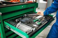 Repairmanhand som når för hjälpmedelasken fotografering för bildbyråer