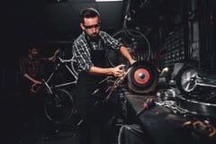Repairmaster pracuje z maszynowym narz?dziem przy ruchliwie bucycle warsztatem fotografia royalty free
