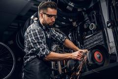 Repairmaster pracuje z maszynowym narz?dziem przy ruchliwie bucycle warsztatem obraz stock
