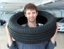 Repairmen automobile mechanic with car tire. In repair service Stock Photography