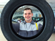 Repairmen automobile mechanic with car tire Royalty Free Stock Images