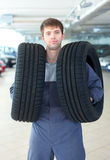 Repairmen automobile mechanic with car tire Royalty Free Stock Image