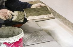 Repairs. Laying of floor ceramic tiles. Men`s hands in gloves with  spatula, spread  cement mortar on  ceramic floor tile. Repairs. Laying of floor ceramic Royalty Free Stock Photo