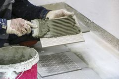 Repairs. Laying of floor ceramic tiles. Men`s hands in gloves with  spatula, spread  cement mortar on  ceramic floor tile. Repairs. Laying of floor ceramic Stock Photo