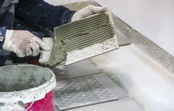 Repairs. Laying of floor ceramic tiles. Men`s hands in gloves with  spatula, spread  cement mortar on  ceramic floor tile. Repairs. Laying of floor ceramic Royalty Free Stock Photography