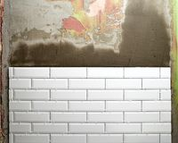 Repairs. Several rows of white tiles are mounted on the wall. Royalty Free Stock Photography