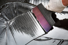 Repairs with a spatula and bitumen. Builder makes repairs with a spatula and bitumen royalty free stock images
