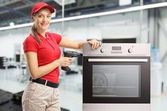 Repairwoman met een boor en oven bij een fabriek die cameraand het glimlachen bekijken royalty-vrije stock foto's