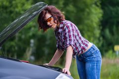 A reparação bonita da jovem mulher herbroken o carro perto da estrada imagem de stock