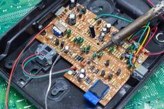 Reparação do técnico eletrônica da placa de circuito do computador por ferros de solda fotografia de stock royalty free