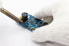 Reparação do técnico eletrônica da placa de circuito por ferros de solda imagens de stock