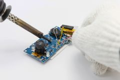 Reparação do técnico eletrônica da placa de circuito por ferros de solda fotografia de stock