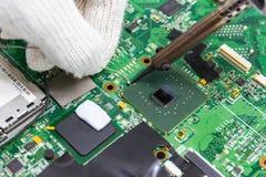 Reparação do técnico eletrônica da placa de circuito do ` s do computador por ferros de solda foto de stock