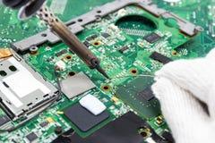 Reparação do técnico eletrônica da placa de circuito do ` s do computador por ferros de solda imagem de stock royalty free