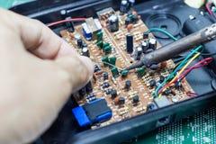 Reparação do técnico eletrônica da placa de circuito do ` s do computador por ferros de solda fotos de stock