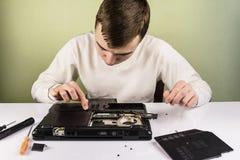 Reparación adolescente un ordenador portátil quebrado Fotos de archivo libres de regalías