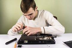 Reparación adolescente un ordenador portátil quebrado Imágenes de archivo libres de regalías
