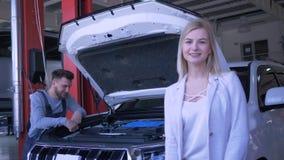 Reparación auto, retrato del propietario de coche del cliente de la mujer durante el trabajo del automóvil de proceso de las repa metrajes