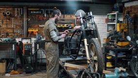 Reparación de la bici Dos hombres con la barba están creando la motocicleta de encargo almacen de video