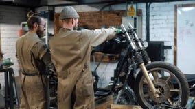 Reparación de la bici Dos hombres con la barba están creando la motocicleta de encargo almacen de metraje de vídeo