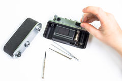 Reparación de la cámara vieja usando el destornillador Foto de archivo