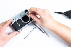 Reparación de la cámara vieja usando el destornillador Fotografía de archivo libre de regalías