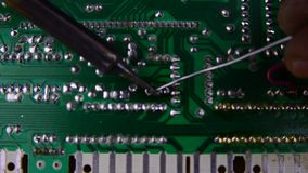 Reparación de la electrónica, soldando con un soldador de los componentes electrónicos del tablero almacen de metraje de vídeo