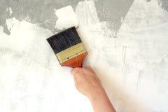 Reparación de la pared del cepillo y de la pintura del control de la mujer Imagen de archivo libre de regalías